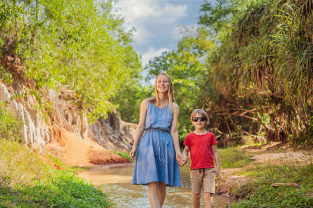 Photo for Mom and son tourists on the Fairy stream among the red dunes, Muine, Vietnam. - Royalty Free Image