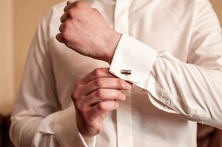Photo for A groom fastening a cuff-link before getting married - Royalty Free Image