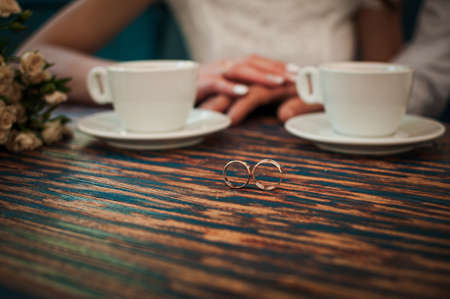 Photo pour Pair of gold wedding rings and two cups of coffee - image libre de droit