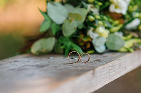 Photo pour Wedding rings on a wooden stand against the background of the bride's bouquet - image libre de droit