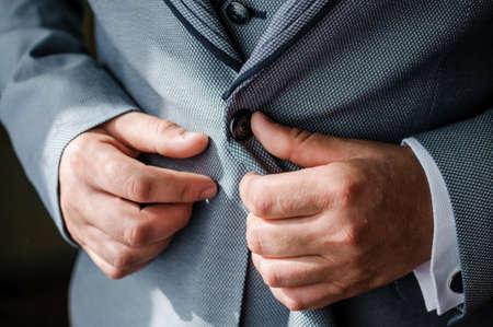 Photo pour The man fasten a button on his jacket. The groom fasten a button on his jacket - image libre de droit