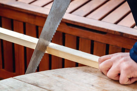 Mens hands sawing a wooden bar with a hacksaw
