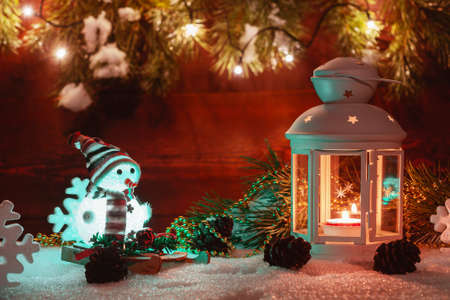 Photo pour White lantern with a burning candle stands in the snow surrounded by Christmas decorations on the background of a wooden wall, Christmas tree branches and lights - image libre de droit