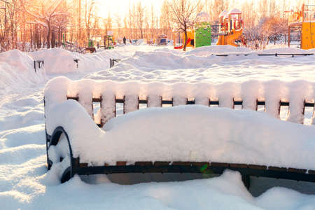 Empty wooden snow covered bench in the town square