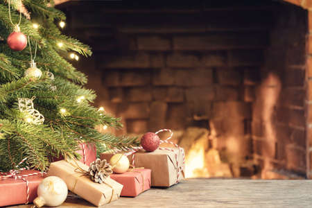 Photo for Gifts under the Christmas tree in the room with a fireplace on Christmas eve - Royalty Free Image