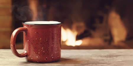 Photo pour Red mug with hot tea in front of a burning fireplace, comfort, winter holidays and warmth of the hearth concept - image libre de droit