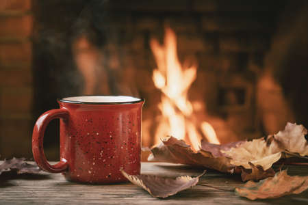 Photo pour Red mug with hot tea in front of a burning fireplace, comfort and warmth of the hearth concept - image libre de droit