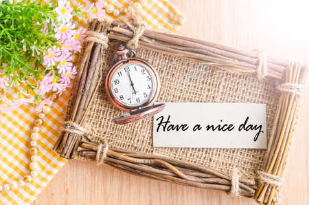 Have a nice day card and pocket watch at 6 AM with flower on wooden background.