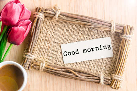 Good morning paper tag in sack photo frame and coffee with red tulip on wooden background.