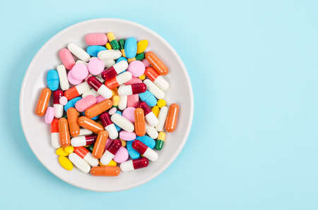 A top view of colourful medicine pills and capsules in white plate on blue background. Copy space for the ads.