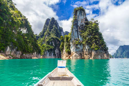 Photo pour Wooden Thai traditional long-tail boat on a lake with mountains at Ratchaprapha Dam or Khao Sok National Park, Surat Thani Province, Thailand - image libre de droit