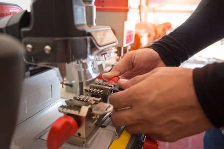 Photo for Locksmith in workshop makes new key. Professional making key in locksmith. Machine production of duplicate metal key. - Royalty Free Image