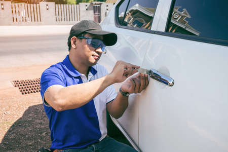 Photo for Young Man Opening White Car Door With Lockpicker. Professional making key in locksmith - Royalty Free Image