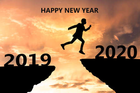 Photo pour Happy New Year 2020 Silhouette. Young man jumps over a cliff in 2019 to a cliff in 2020. Sunset time - image libre de droit