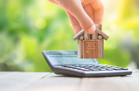 Photo pour When the man who is home is put on the calculator. planning savings money of coins to buy a home concept for property, mortgage and real estate investment.to buy a house. - image libre de droit