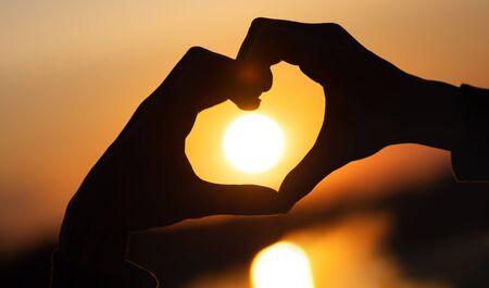 Foto de silhouette hands forming a heart shape with sunset and reflection of a solar track in the water - Imagen libre de derechos