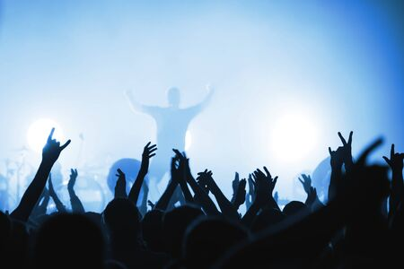 Photo pour Blurred silhouettes of rock band musicians with beautiful lighting on stage and crowds at a concert. atmosphere of a music festival. light spotlights - image libre de droit