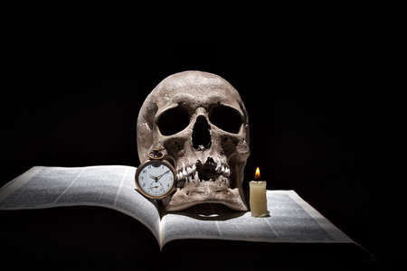Photo pour Human skull on old open book with burning candle and vintage clock on black background under beam of light. - image libre de droit