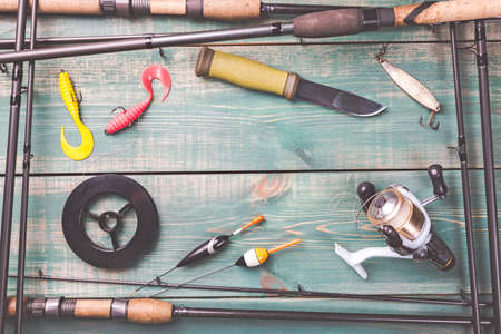 Photo pour Fishing theme. Frame from fishing rods with fishing tackles, line, knife, reel and fishing buoy on green wooden background - image libre de droit