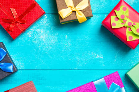 Colorful gift boxes with ribbons on nice blue wooden background. Copy space. Christmas or birthday celebration holiday theme