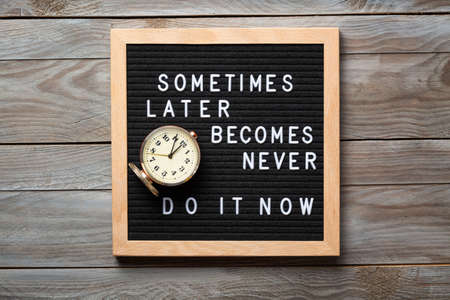 Photo pour Inspirational motivational quote Sometimes later becomes never. Do it now words on a letter board on wooden background near vintage alarm clock. Success and motivation concept - image libre de droit