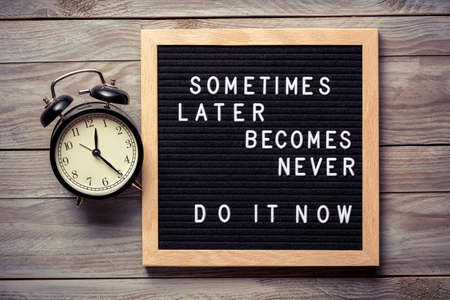Foto de Inspirational motivational quote Sometimes later becomes never. Do it now words on a letter board on wooden background near vintage alarm clock. Success and motivation concept - Imagen libre de derechos