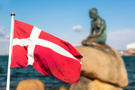 Photo for The Little Mermaid statue in Copenhagen with Denmark flag. Very popular tourist attraction - Royalty Free Image