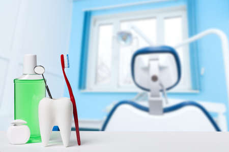 Photo for Dental health and teethcare concept. Dental mirror in white tooth model near mouthwash, toothbrush and dental floss against dental office and chair background. - Royalty Free Image