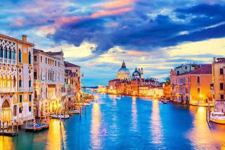 Foto per Basilica Santa Maria della Salute, Punta della Dogona and Grand Canal at blue hour sunset in Venice, Italy with boats and reflections - Immagine Royalty Free