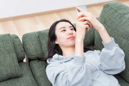 Photo for A woman who lays down and operates her smartphone - Royalty Free Image