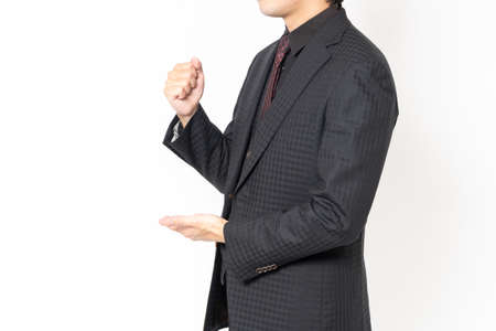 Photo pour A male businessman standing in front of a white background and making a convincing gesture - image libre de droit