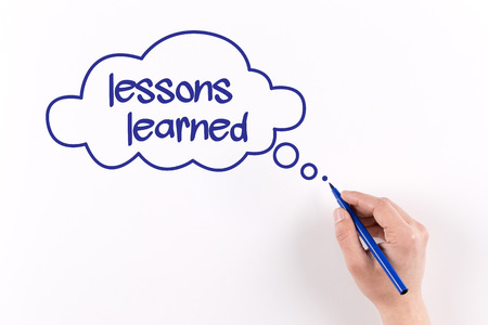 Hand writing Lessons learned on white paper, View from above