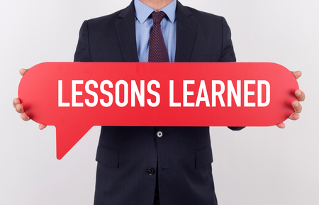 Businessman holding speech bubble with a word LESSONS LEARNED