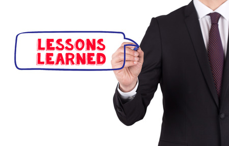 Hand writing a word LESSONS LEARNED on white board
