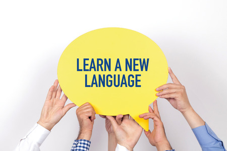 Group of people holding the LEARN A NEW LANGUAGE written speech bubble