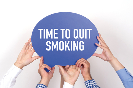 Group of people holding the TIME TO QUIT SMOKING written speech bubble