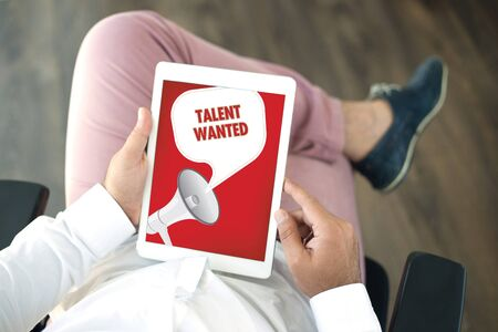 People using tablet pc and TALENT WANTED announcement concept on screen