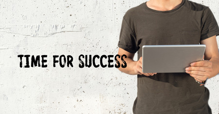 Young man using tablet pc and TIME FOR SUCCESS concept on wall background