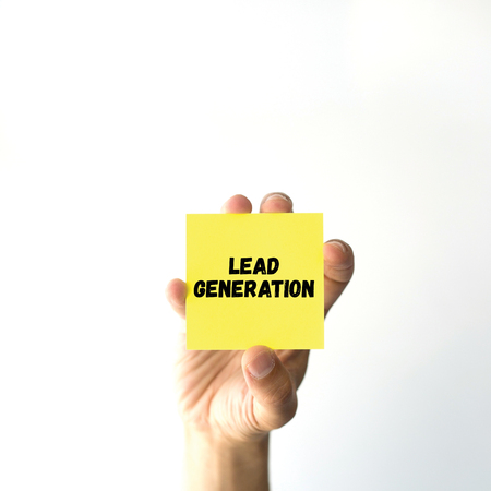 Hand holding yellow sticky note written LEAD GENERATION word