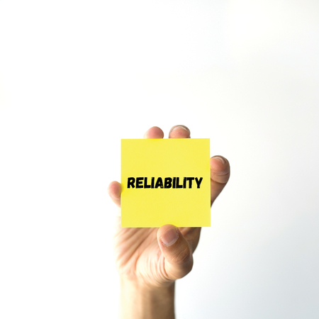 Hand holding yellow sticky note written RELIABILITY word