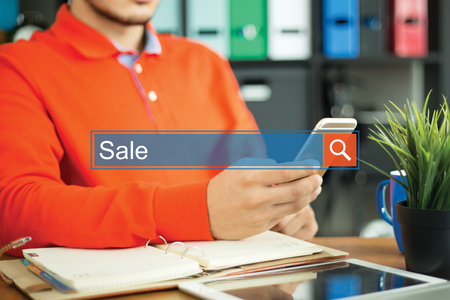 Young man using smartphone and searching SALE word on internet