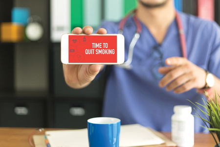 Young and professional medical doctor showing a smartphone and TIME TO QUIT SMOKING concept on screen