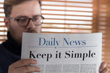 Man reading Keep it Simple headlined newspaper