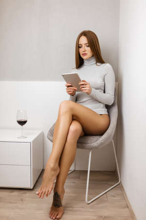 Foto de Young lady in sweater sitting with tablet in hands thoughtfully looking on it with glass of wine - Imagen libre de derechos