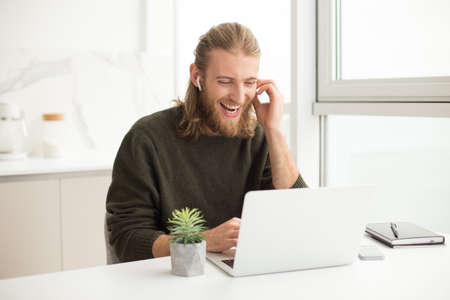 Photo pour Young joyful man in earphones sitting at the table and laughing while looking in laptop at home - image libre de droit