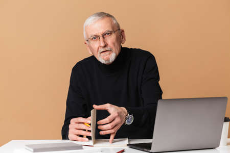 Photo pour Old man with gray hair and beard in eyeglasses and sweater sitting at the table with laptop and notebook thoughtfully looking in camera over beige background isolated - image libre de droit