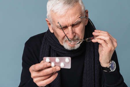 Photo pour Old pensive sick man with gray hair and beard in eyeglasses and scarf thoughtfully looking on pills over blue background isolated - image libre de droit
