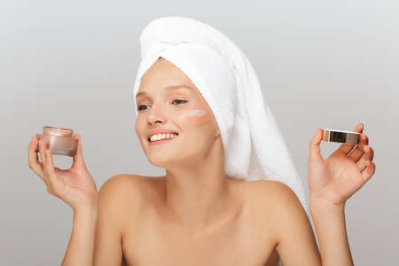 Photo pour Portrait of young joyful woman with white towel on head without makeup holding face cream in hand happily looking aside with cream on cheek over gray background isolated - image libre de droit