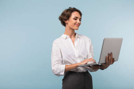 Photo pour Young smiling businesswoman with dark short hair in white shirt happily working on laptop over blue background isolated - image libre de droit