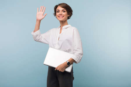 Photo pour Young smiling businesswoman with dark short hair in white shirt showing hi gesture with laptop in hand while happily looking in camera over blue background - image libre de droit